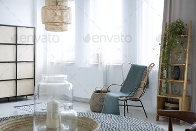 Green blanket on armchair in bright living room interior with pl