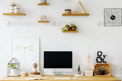 Poster and desktop computer on wooden desk in white home office