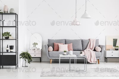 Real photo of a living room interior with a sofa, pillows, table