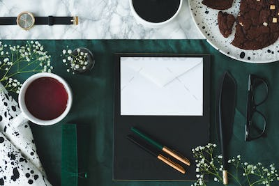 Top view of cup of tea next to white envelope on green backgroun