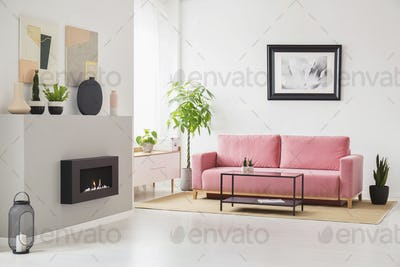 Posters on walls in Scandi sitting room interior with pink velve