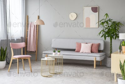 Real photo of lounge with dirty pink pillows, simple poster, pin