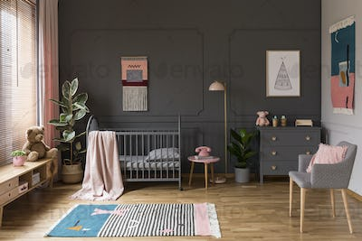 Real photo of a grey crib standing next to a pink stool, a lamp