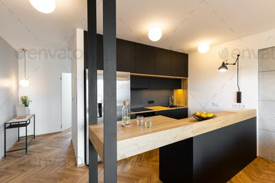 Lights in black kitchen interior with bright modern countertop a