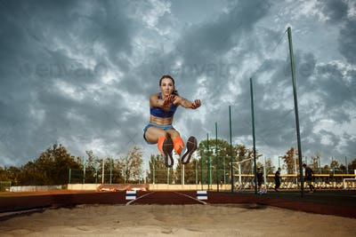 Female athlete performing a long jump during a competition