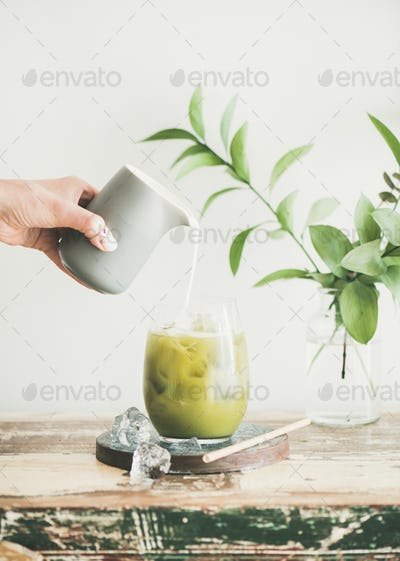 Iced matcha latte drink with coconut milk in glass
