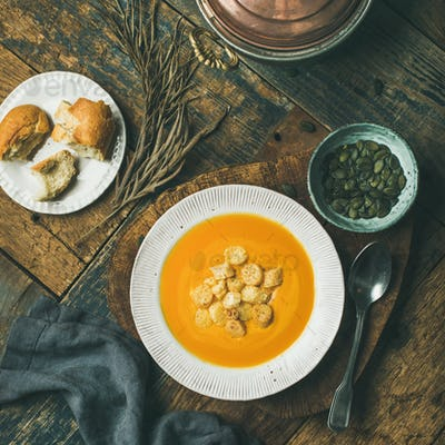 Warming pumpkin cream soup with croutons and seeds on board