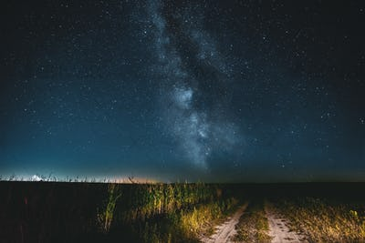Night Starry Sky With Milky Way Glowing Stars Above Country Road