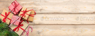 Gift boxes with red ribbons and candy canes on wooden background, banner, copy space, top view