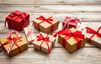 Gift boxes with red ribbons on wooden background, copy space