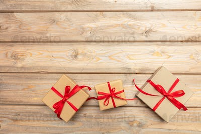 Gift boxes with red ribbon on wooden background, copy space, top view