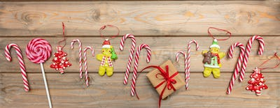 Candy canes, christmas ornaments and a gift box with red ribbon on wooden background, banner