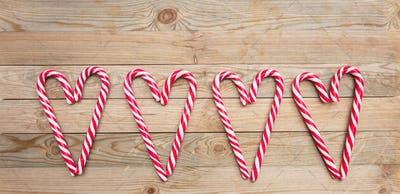 Candy canes heart shaped on wooden background