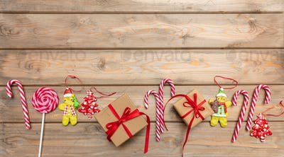 Candy canes, christmas ornaments and a gift box with red ribbon on wooden background, copy space