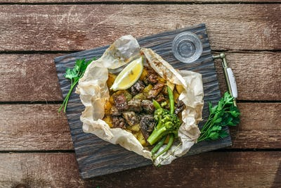 Lamb kleftiko, potato and vegetables served on wooden cutin board, rustic style
