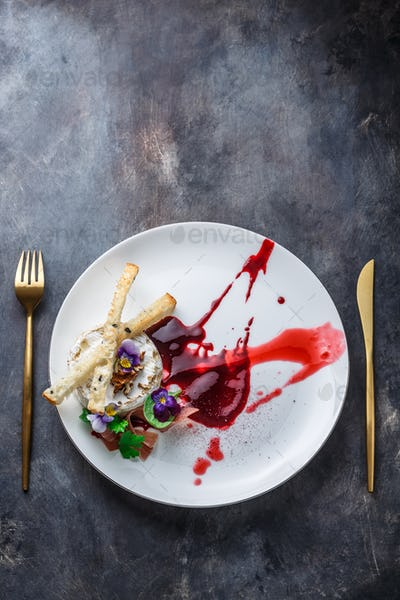 Grilled camambert cheese with jam and walnuts on white plate, restaurant meal, copy space.