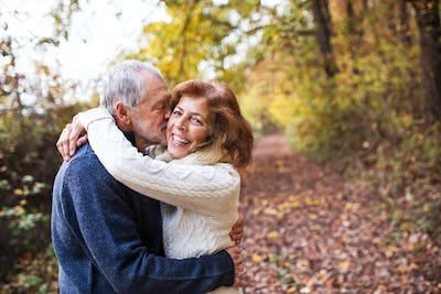 A senior couple hugging in an autumn nature, kissing. Copy space.