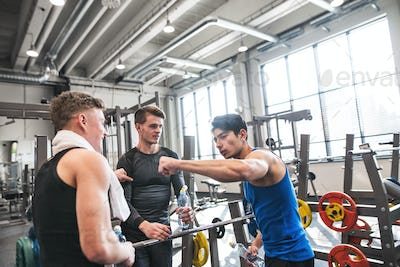 Young friends standing and talking in modern crossfit gym, holding plastic bottles.