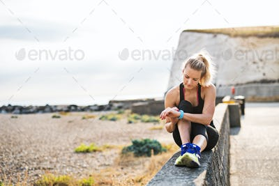 Young sporty woman runner resting outside in nature, setting smartwatch.