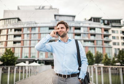 A young businessman with a smartphone walking on a bridge.