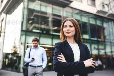 A portrait of a young businesswoman standing outdoors in front of a building.
