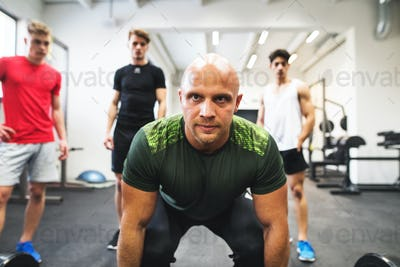 Fit young men looking at a personal trainer in gym lifting barbell.