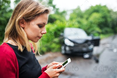 A young woman with smartphone by the damaged car after a car accident, text messaging.
