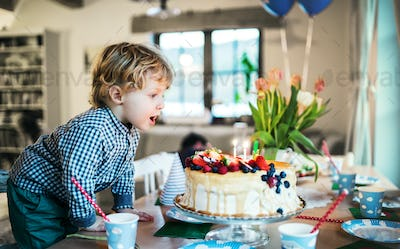 A boy standing on a chair, blowing out candles on a birthday cake.