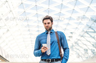 A young businessman with smartphone walking in a modern building, texting.