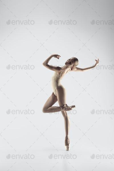 Ballerina. Young graceful female ballet dancer dancing at studio. Beauty of classic ballet.