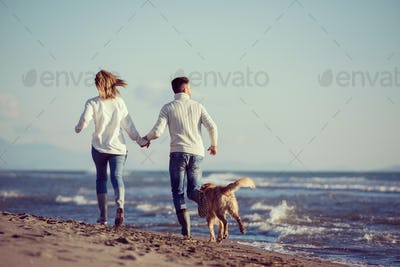couple with dog having fun on beach on autmun day