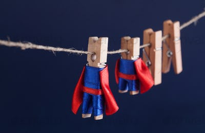 Super team concept photo with clothespin superheroes in blue suit and red cape.