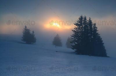foggy sunrise on snowy mountain top