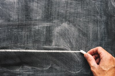 Hand underlining with chalk on school blackboard