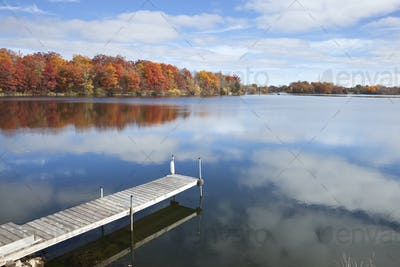 Calm Minnesota lake with dock on colorful autumn day