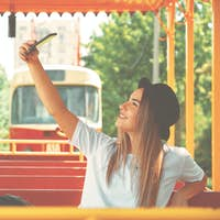 An attractive girl takes pictures for her blog while travel