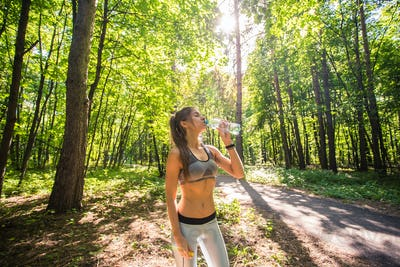 Young woman drinking water after running outdoors