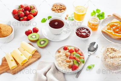 healthy breakfast with oatmeal porridge, strawberry, nuts, toast