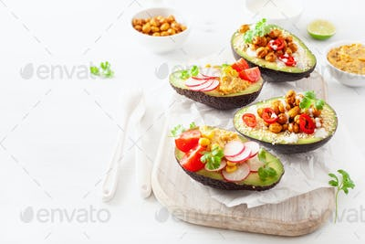 avocado boats stuffed with hummus, tomatoes, radish, roasted chi