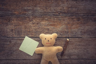 Adorable teddy bear holding sticky note and pencil on wooden table. Space for text
