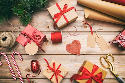 Christmas gift boxes wrapping on wooden background, top view