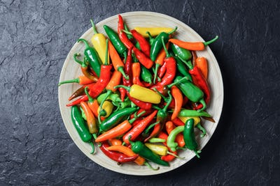 Different colors hot peppers in wooden plate