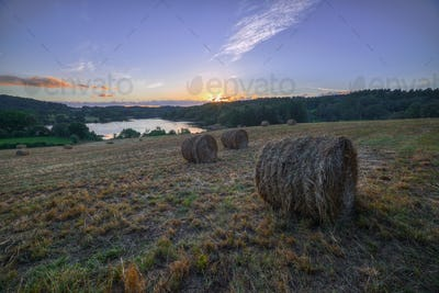 Sunset in a field with bales of straw