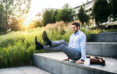 A happy businessman outdoors on stairs at sunset., handstand in L-sit position.