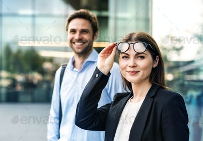 A portrait of young businessman and businesswoman standing outdoors.