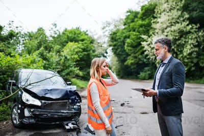 An insurance agent talking to a woman driver by the car on the road after an accident.