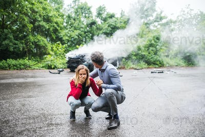 A mature man talking to a stressed young woman after a car accident.