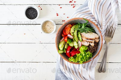 Buddha bowl dish with chicken fillet, quinoa, avocado, sweet pepper, tomato, cucumber, radish