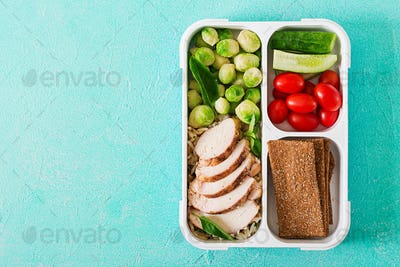 Healthy green meal prep containers with chicken fillet, rice, brussels sprouts and vegetables
