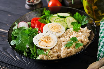 Healthy salad of fresh vegetables - tomatoes, cucumber, radish, egg, arugula and oatmeal on bowl.